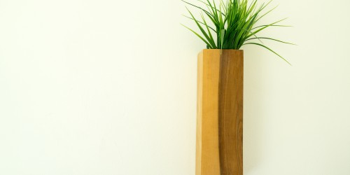 Wooden flowerpot with green grass hung on the wall.